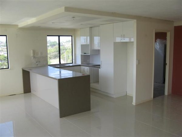 Compact Apartment Kitchen, Stone Tops, Open Galley Style, Drop Ceiling above for Down Lights, Tiled Splashback